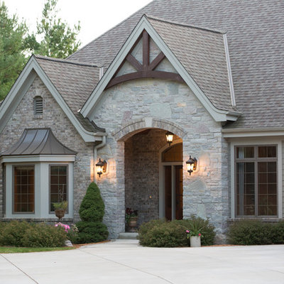 Inspiration for a huge timeless beige one-story stone exterior home remodel in Milwaukee with a shingle roof