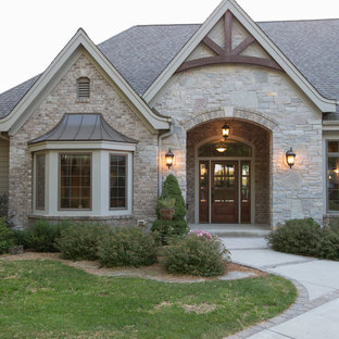 Huge traditional beige one-story stone exterior home idea in Milwaukee with a shingle roof