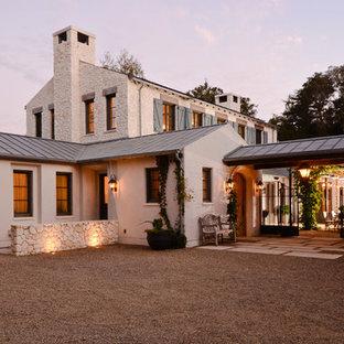 Foto de fachada beige, mediterránea, de dos plantas, con revestimientos combinados y tejado de metal