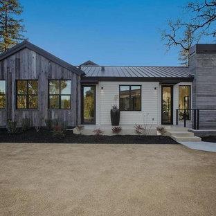 Foto della facciata di una casa unifamiliare grande grigia moderna a un piano con rivestimenti misti, tetto a padiglione e copertura verde