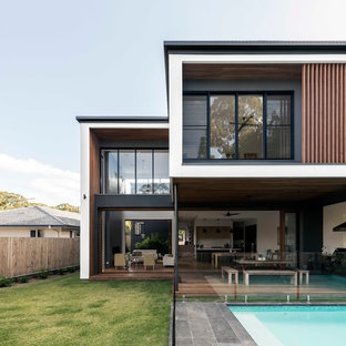Design ideas for a contemporary two-storey multi-coloured house exterior in Brisbane with mixed siding and a flat roof.