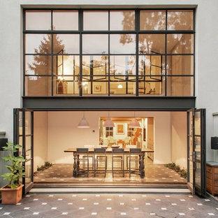 На фото: двухэтажный, стеклянный, белый частный загородный дом среднего размера в стиле современная классика с плоской крышей