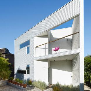 Imagen de fachada blanca, contemporánea, de tamaño medio, de dos plantas, con revestimiento de metal