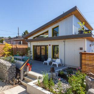 Foto della facciata di una casa unifamiliare grigia industriale a due piani di medie dimensioni con rivestimento in metallo, tetto a una falda e copertura in metallo o lamiera