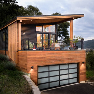 Example of a mid-century modern black metal house exterior design in Portland with a shed roof and a metal roof