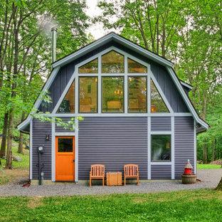 Diseño de fachada gris, campestre, de dos plantas, con revestimiento de madera y tejado a doble faldón