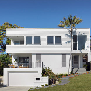 Inspiration for a beach style white house exterior in Sydney with three or more storeys and a flat roof.