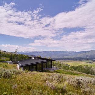 На фото: большой, одноэтажный, черный частный загородный дом в стиле модернизм с облицовкой из металла, односкатной крышей и металлической крышей с