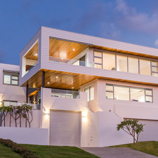 This is an example of a large contemporary white house exterior in Perth with three or more storeys, mixed siding and a flat roof.