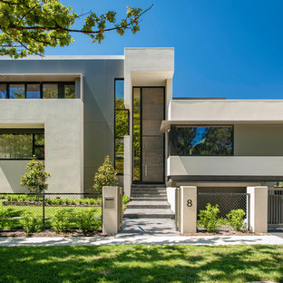 Photo of a contemporary two-storey concrete beige house exterior in Canberra - Queanbeyan with a flat roof.
