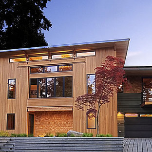 Example of a large minimalist brown two-story wood flat roof design in Seattle