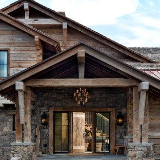 Foto della facciata di una casa unifamiliare grande marrone rustica a due piani con rivestimento in legno, tetto a mansarda e copertura mista