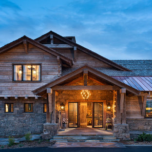 Example of a huge mountain style brown two-story wood house exterior design in Other with a gambrel roof and a mixed material roof