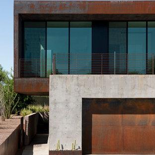 Esempio della facciata di una casa grigia moderna a piani sfalsati di medie dimensioni con rivestimento in metallo e tetto piano