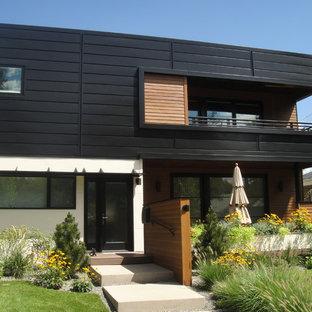 Inspiration för mellanstora moderna svarta hus, med två våningar, metallfasad och platt tak