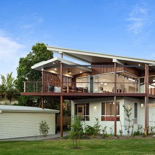Ejemplo de fachada de casa multicolor, marinera, de dos plantas, con revestimientos combinados y tejado de un solo tendido