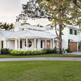 Example of a coastal white two-story house exterior design in Miami with a hip roof and a metal roof