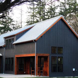 Пример оригинального дизайна: двухэтажный, деревянный, черный частный загородный дом среднего размера в стиле кантри с двускатной крышей и металлической крышей