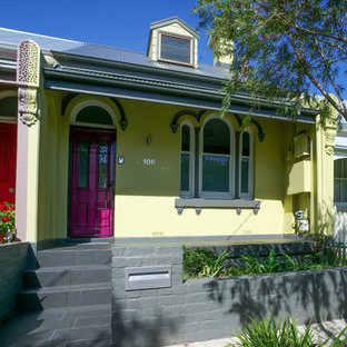Inspiration for a small victorian yellow two-story brick flat roof remodel in Sydney