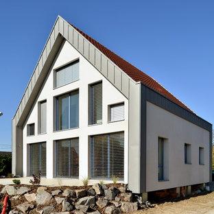 Idée de décoration pour une grand façade de maison blanche design à un étage avec un revêtement mixte et un toit à deux pans.