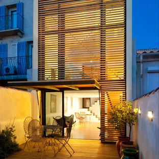 Cette photo montre une petit façade en bois blanche tendance à un étage avec un toit plat.