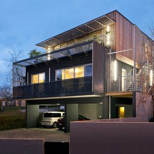 Inspiration pour une façade en bois design à deux étages et plus et de taille moyenne avec un toit plat.