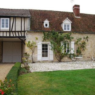 Idée de décoration pour une grand façade en pierre beige champêtre à un étage avec un toit à deux pans.