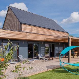 Cette photo montre une grande façade en bois grise tendance à un étage avec un toit à deux pans.