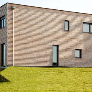 Réalisation d'une façade en bois marron minimaliste de taille moyenne et à un étage avec un toit plat.