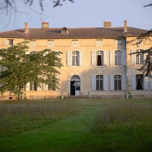 Cette photo montre une grand façade en pierre beige chic à deux étages et plus avec un toit à quatre pans.