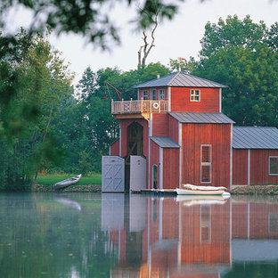 Cette photo montre une petite façade en bois rouge scandinave à un étage avec un toit à quatre pans et un toit en métal.