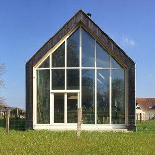 Modelo de fachada negra, actual, de tamaño medio, de tres plantas, con revestimiento de madera y tejado a dos aguas