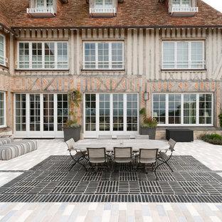 Idée de décoration pour une grand façade de maison champêtre à deux étages et plus avec un toit à quatre pans.