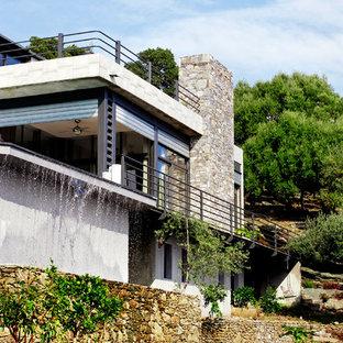 Aménagement d'une façade de maison beige contemporaine de taille moyenne et à deux étages et plus avec un revêtement mixte et un toit plat.