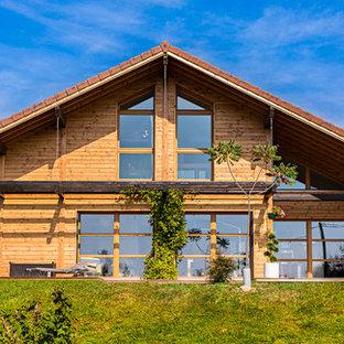 Réalisation d'une grand façade en bois marron chalet à un étage avec un toit à deux pans.