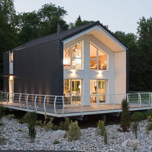 Cette image montre une façade en bois noire design à un étage et de taille moyenne avec un toit à deux pans.
