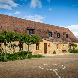 Réalisation d'une façade de maison beige champêtre à un étage avec un toit à quatre pans et un toit en tuile.