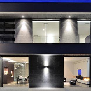 Réalisation d'une façade en pierre grise design de taille moyenne et à un étage avec un toit plat.
