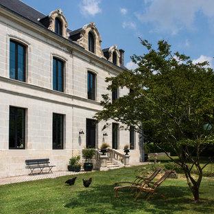 Imagen de fachada de casa beige, bohemia, grande, de tres plantas, con revestimiento de piedra, tejado a cuatro aguas y tejado de teja de barro