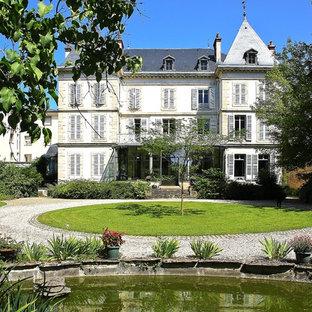 Cette photo montre une grand façade de maison blanche chic à deux étages et plus avec un toit à quatre pans.