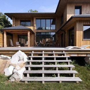 Exemple d'une grand façade de maison marron tendance à un étage avec un toit à quatre pans et un toit en tuile.