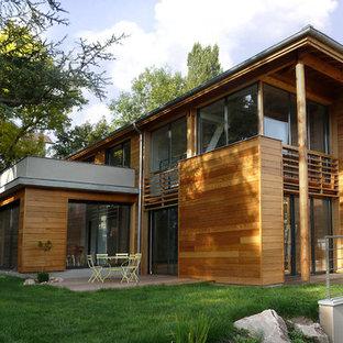 Aménagement d'une façade en bois marron contemporaine à deux étages et plus avec un toit plat.