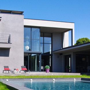Idées déco pour une façade de maison grise contemporaine à un étage et de taille moyenne avec un revêtement mixte et un toit plat.
