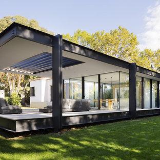 Aménagement d'une façade de maison noire moderne de taille moyenne et à un étage avec un toit plat.