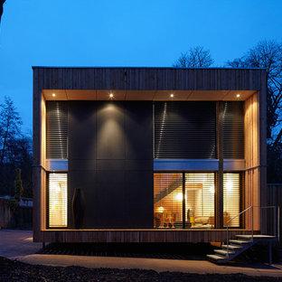 Idées déco pour une façade en verre noire contemporaine à un étage et de taille moyenne avec un toit plat.