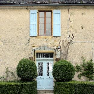 Exemple d'une façade de maison beige chic de taille moyenne et à un étage avec un revêtement en stuc et un toit à deux pans.