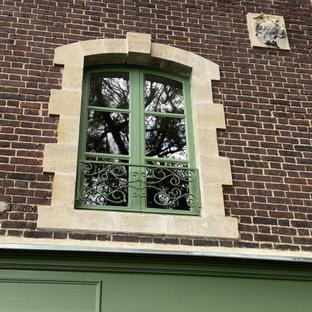 他の地域のエクレクティックスタイルのおしゃれな家の外観 (レンガサイディング、緑の外壁、アパート・マンション) の写真