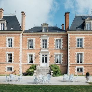 Inspiration pour une grand façade en brique rouge traditionnelle à deux étages et plus avec un toit à quatre pans.