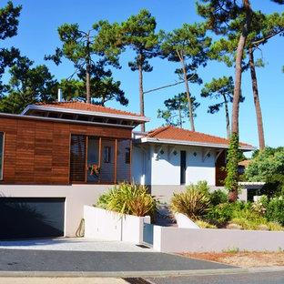 Cette image montre une façade de maison blanche design de taille moyenne avec un revêtement mixte et un toit à quatre pans.