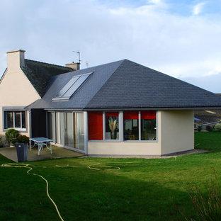 Imagen de fachada gris, de estilo de casa de campo, de tamaño medio, de una planta, con revestimiento de vidrio y tejado a dos aguas
